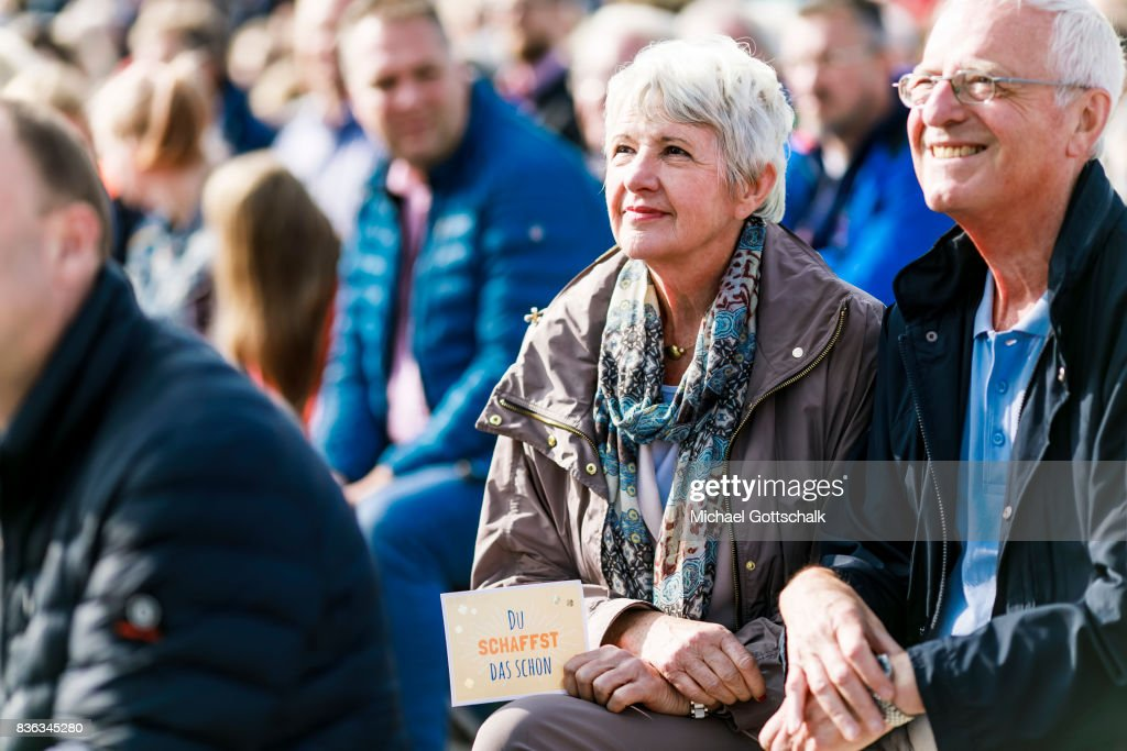 A visitor holds a postcard reading Du schaffst das schon or you will do it during German Chancellor Angela Merkels election campaign for Bundestagswahl 2017 or Federal election 2017 on August 21, 2017 in Sankt Peter-Ording, Germany.