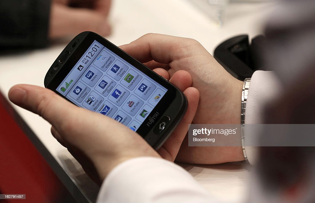 A visitor holds a Stylistic S01 smartphone in the Fujitsu Ltd. pavilion at the Mobile World Congress in Barcelona, Spain, on Wednesday, Feb. 27, 2013. The Mobile World Congress, where 1,500 exhibitors converge to discuss the future of wireless communication, is a global showcase for the mobile technology industry and runs from Feb. 25 through Feb. 28. Photographer: Simon Dawson/Bloomberg via Getty Images