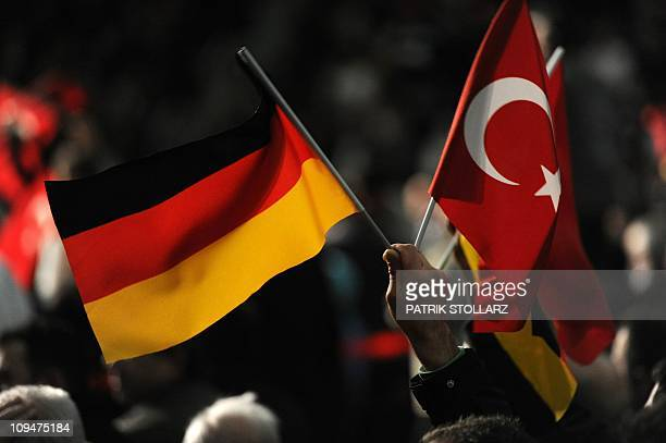 A visitor holds a Turkish and a German flag during a Turkish cultural event where Turkish Prime Minister Recep Tayyip Erdogan was expected on...
