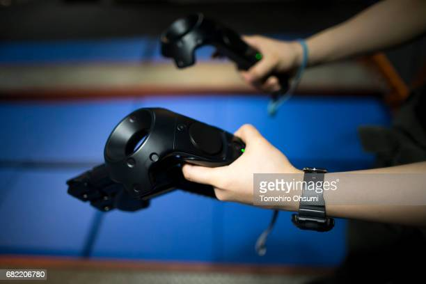 A visitor holds controllers for the HTC Corp Vive VR headset as he plays the Dive Hard virtual reality video game at the VR Park Tokyo on May 12 2017...
