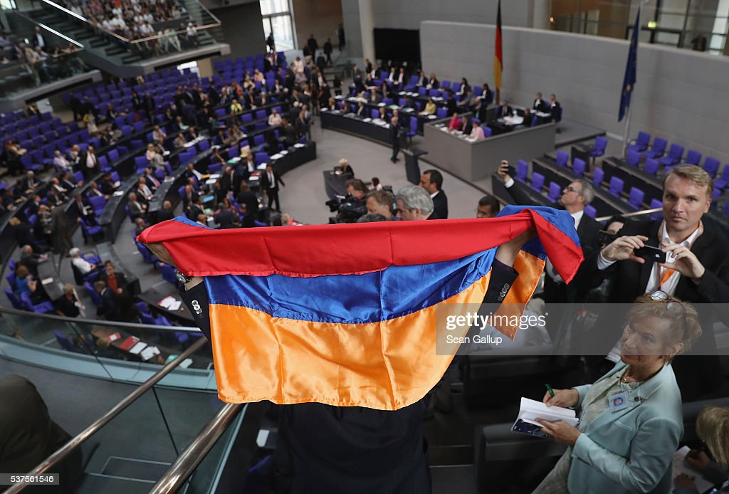 A visitor holds up an Armenian flag after parliamentarians approved with a show of hands a resolution to recognize the 1915 Armenian genocide on June 2, 2016 in Berlin, Germany. The Bundestag approved a resolution recognizing the 1915-1916 deaths of hundreds of thousands of Armenians and other ethnic groups at the hands of Ottoman Turkish forces. The Turkish government has opposed any labeling of the deaths as genocide and the approval will likely irritate German-Turkish relations.