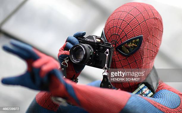 A visitor in a costume of fictional superhero Spiderman takes pictures during the Leipzig Book Fair on March 14 2015 The Leipzig book fair hosts 2263...