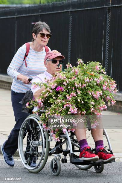 Visitor in a wheelchair to the RHS Chelsea Flower Show seen carrying flowers during the final day of the show. The Royal Horticultural Society...