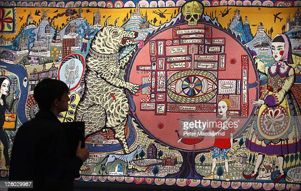 A visitor in silouhette in front of Grayson Perry's tapestry 'Map of Truths and Beliefs' on display at The Tomb of the Unknown Craftsman exhibition...