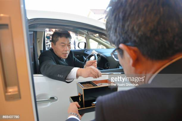 A visitor in the driving seat offers incense at a firstever 'DriveThrough' funeral hall during a press preview on December 15 2017 in Ueda Nagano...