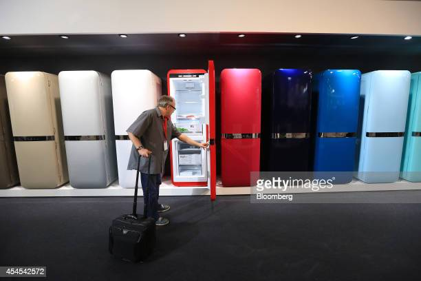 A visitor inspects a range of colored domestic refrigerators on display at the Robert Bosch GmbH trade stand at the IFA Consumer Electronics Fair in...
