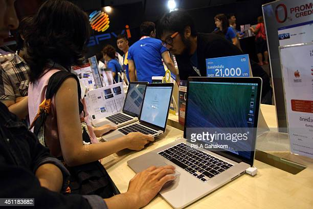 Visitor inspects Mac Book Pro at the Commart NextGen 2014 in Bangkok One of the most comprehensive events for new technology and innovative IT...