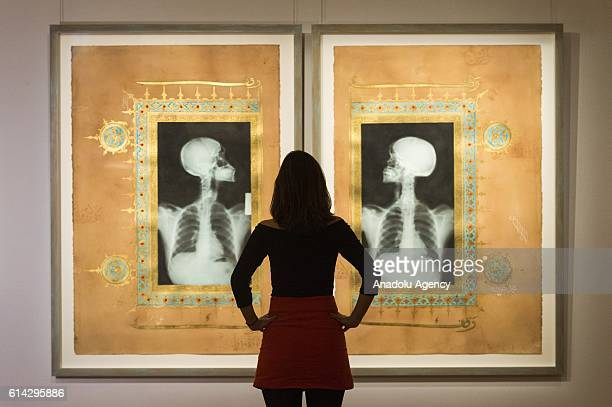 A visitor inspects the artwork titled 'Illumination XIX XX' by the Saudi artist Ahmed Mater with an estimate of £1800025000 on display as part of a...
