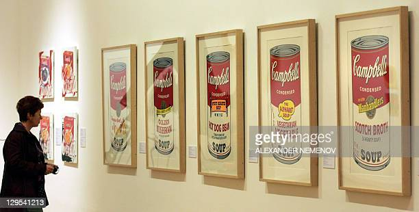 A visitor inspects the famous 'Campbells Soup' installation at Andy Warhol's art exhibition in Moscow 13 September 2005 AFP PHOTO/ ALEXANDER NEMENOV