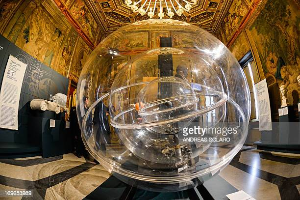 A visitor interacts passes by a reproduction of Greek scientist Archimedes' 'Planetarium' during the 'Archimedes art and science of the inventor'...