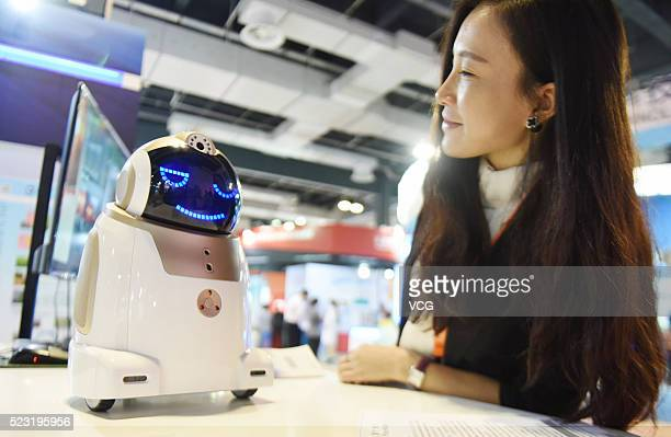 A visitor interacts with a household security robot during the opening ceremony of the 4th China International Technology Fair at Shanghai World Expo...