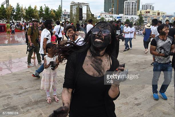 Visitor is daubed rice ash on face during the Face Painting Festival in Puzhehei Resort of Qiubei County on July 18, 2016 in Wenshan Prefecture,...