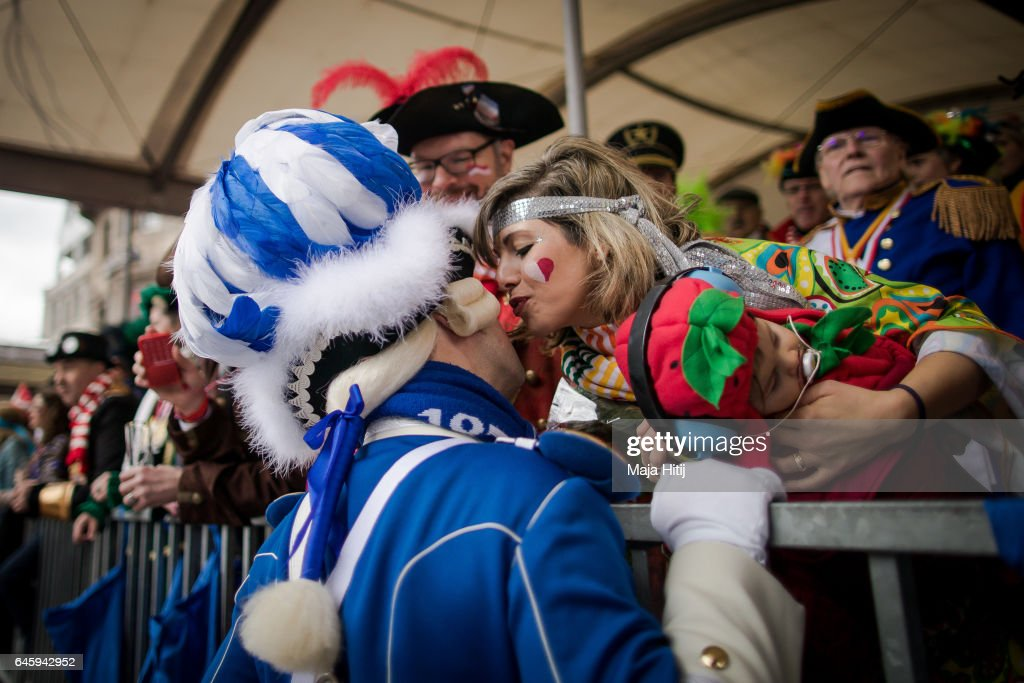 Visitor is kissed by a carnival member during Rose Monday parade on February 27, 2017 in Cologne, Germany. Political satire is a traditional cornerstone of the annual parades and the ascension of Donald Trump to the U.S. presidency, the rise of the populist far-right across Europe and the upcoming national elections in Germany provided rich fodder for float designers this year.