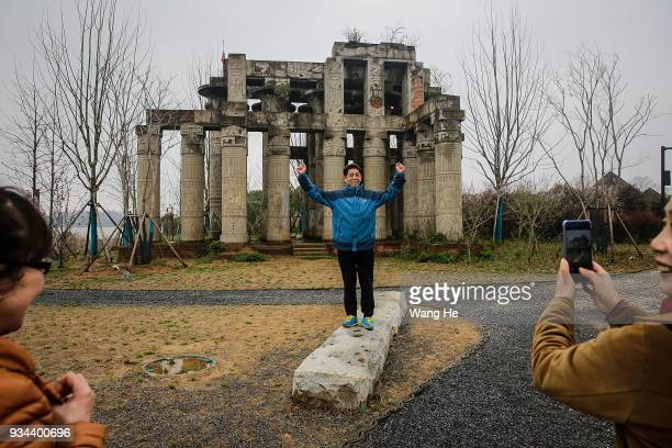 A visitor is photographed in front of a replica of the Karnak Temple in Egypt at the abandoned Wanguo Park on March 19 2018 in Wuhan Hubei...