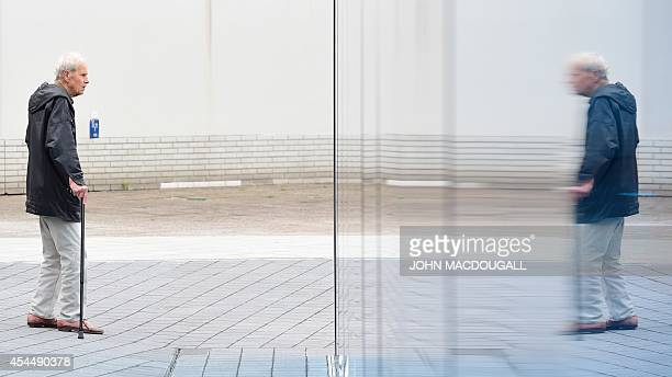 A visitor is reflected in the memorial to the victims of the Nazis' 'euthanasia' programme in Berlin on September 2 2014 prior to its official...