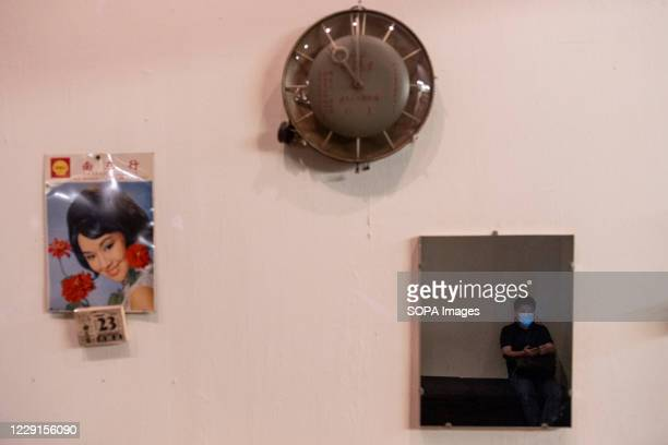 Visitor is seen at a mirror sitting at a bench as he takes a break during an exhibition at the Hong Kong museum of History. The permanent exhibition...
