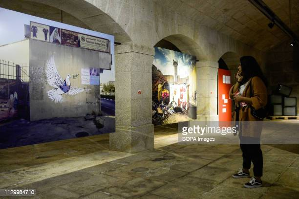 A visitor is seen walking by dove and flak jacket image during Banksy´s Dismaland and Others exhibition at Alfandega Congress Center The exhibition...