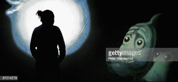 A visitor is silhouetted against a giant screen projection at the Pixar 20 Years of Animation exhibition at the Science Museum on March 30 2006 in...