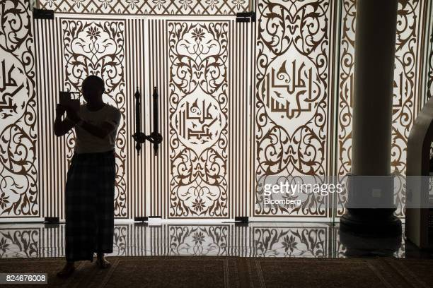 A visitor is silhouetted while using a smartphone to take a photograph at the Crystal Mosque in Kuala Terengganu Terengganu Malaysia on Monday July...