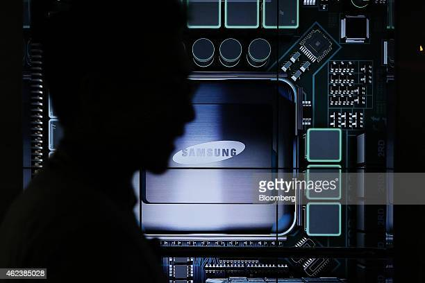 A visitor is silhouetted while walking past the Samsung Electronics Co logo displayed at the Semiconductor Rider experience at the company's d'light...