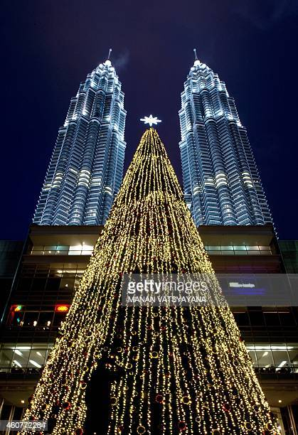 A visitor is silhoutted infront of an illuminated Christmas tree in the backdrop of Malaysia's iconic twintowers at a shopping mall in Kuala Lumpur...