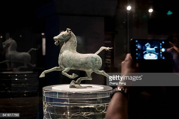 Visitor is taking picture of Bronze Flying Horse with mobile phone in Gansu Provincial Museum. Bronze Flying Horse, from East Han Dynasty, depicting...