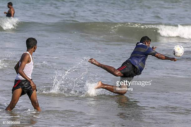 Visitor jumps for a football while in the sea at Velankanni Beach in Nagapattinam, Tamil Nadu, India, on Saturday, Oct. 15, 2016. India's new central...