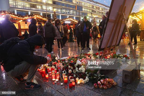 A visitor lays a candle at a makeshift memorial inside the reopened Breitscheidplatz Christmas market only a short distance from where three days ago...