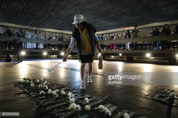 A visitor lays down a flower on the name of a former concentration camp during her visit of the Hall of Remembrance at Yad Vashem Holocaust Memorial...