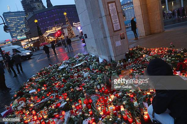 A visitor lays flowers at a makeshift memorial just outside the reopened Breitscheidplatz Christmas market only a short distance from where three...
