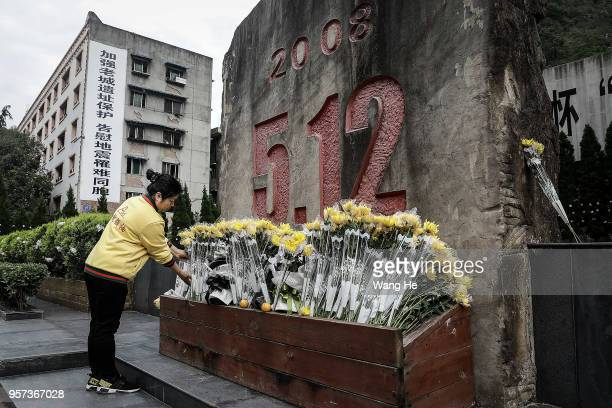A visitor lays flowers to mourn for the victims at the ruins of earthquakehit Beichuan county during the ten year anniversary on May 11 2018 in...