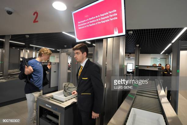 A visitor leaves his belongings to walk through security screening before accessing the Sagrada Famila Basilica in Barcelona on January 3 2018 The...