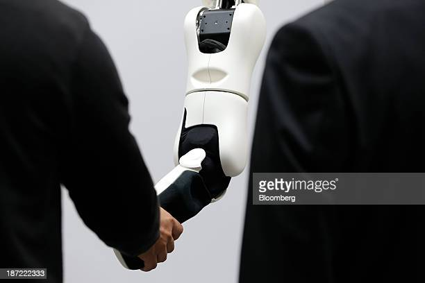 A visitor left shakes hands with Toyota Motor Corp's research and developmentbased torque servo robot arm next to an attendant at the International...