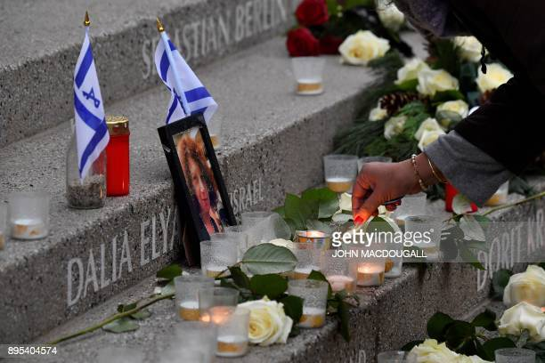 A visitor lights a candle in front of a portrait of killed Israeli tourist Dalia Elyakim at the memorial for the victims of last year's deadly truck...