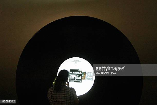 A visitor listens to an album in a long play machine during an exhibition to celebrate the 50th anniversary of Brazilian movement and musical style...