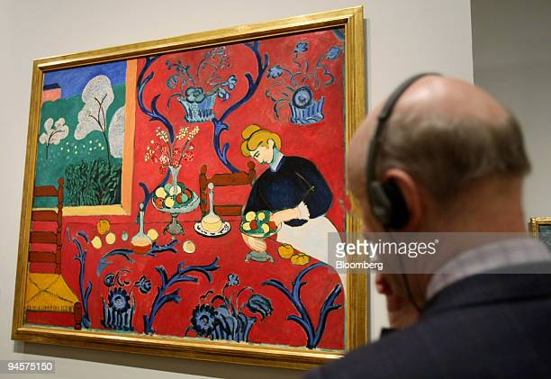 Visitor listens to an audio commentary as he looks at Henri Matisse's painting ''The Red Room'' at the exhibition ''From Russia: French and Russian...