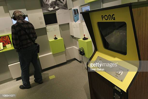 A visitor listens to an audio presentation next to a standing console of Pong one of the earliest commercially successful video games at the Computer...