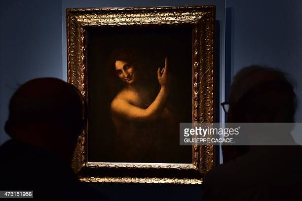 Visitor look at a painting representing John the Baptist by Italian master Leonardo Da Vinci presented at the Palazzo Reale museum as part of the...