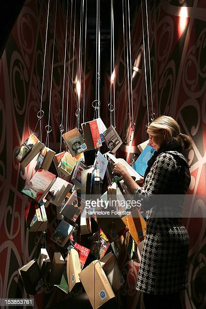 A visitor look at hanging books at the New Zealand stand at the Frankfurt Book Fair on October 10 2012 in Frankfurt Germany The Frankfurt Book Fair...
