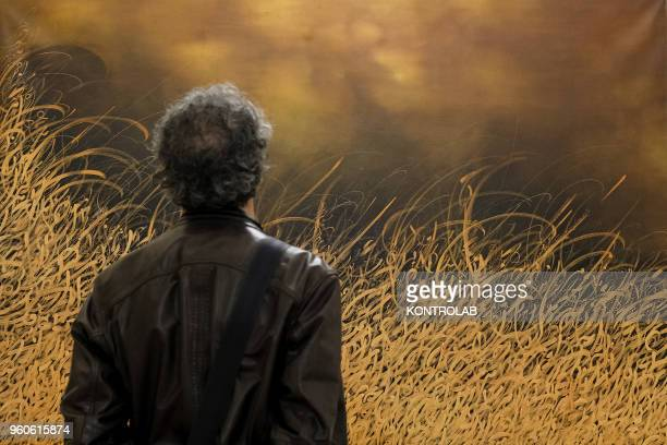 PIEMONTE SALUZZO CUNEO ITALY Visitor looks a painting of Iranian artist Alireza Karimpour during the opening of exhibition Diario Persiano at...