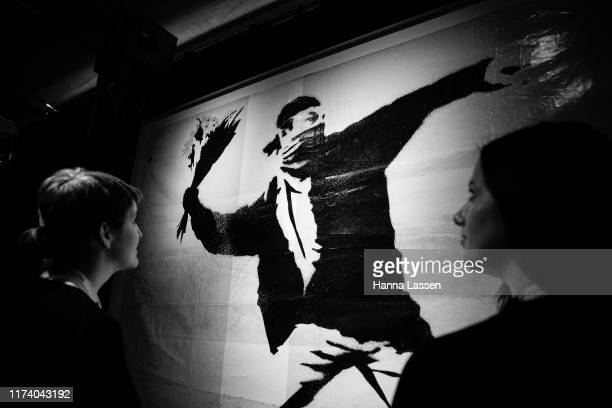 A visitor looks an artwork by Banksy during a media preview for The Art of Banksy on September 12 2019 in Sydney Australia