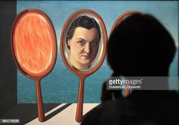 A visitor looks an artwork by Belgian surrealist artist Rene Magritte at the Magritte Museum in Brussels on May 17 ahead of a series of exhibitions...