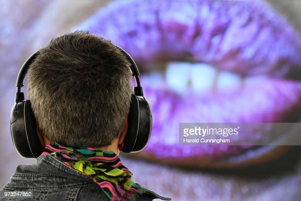 A visitor looks and listens to the artwork of Candice Breitz 'Sweat' during the press preview for Art Basel at Basel Messe on June 13 2018 in Basel...