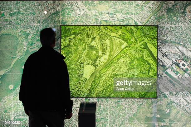 A visitor looks at a backlit map as part of a presentation highlighting the benefits of the Stuttgart 21 train station project in Hauptbahnhof train...