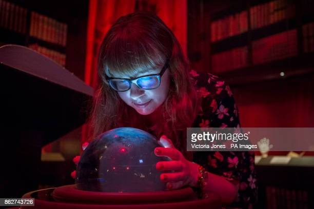 A visitor looks at a crystal ball giving a visual representation of divination for visitors during a press preview for the Harry Potter A History of...