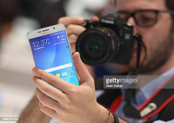 A visitor looks at a Galaxy Note 5 smartphone at the Samsung stand during a press day at the 2015 IFA consumer electronics and appliances trade fair...