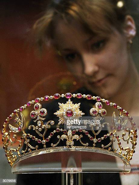 A visitor looks at a golden diadem exhibited in the Hermitage museum in StPetersburg 01 March 2004 The diadem decorated with 822 diamonds and 70...