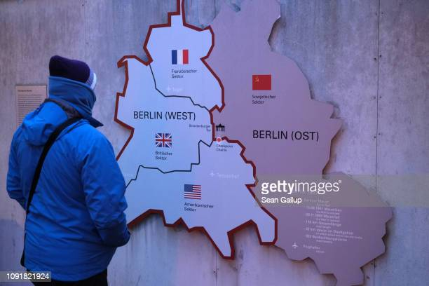 A visitor looks at a map of the Cold War zones of US British French and Soviet occupation of West and East Berlin at an outdoor exhibit near the site...