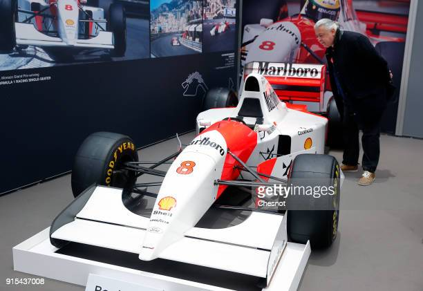 A visitor looks at a McLarenFord MP4/8A during a press preview before a mass auction of vintage vehicles organised by Bonhams auction house at the...