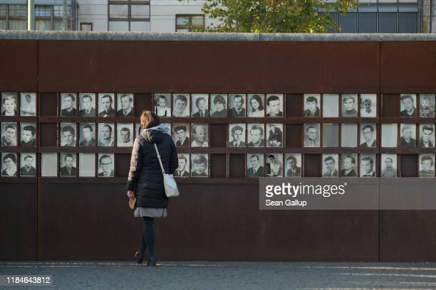 A visitor looks at a memorial to people who died trying to breech the Berlin Wall at the Bernauer Strasse memorial site on October 31 2019 in Berlin...